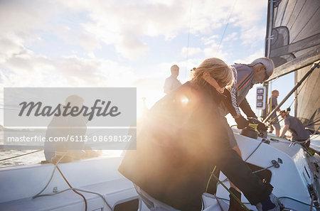 Friends adjusting sailing equipment on sunny sailboat