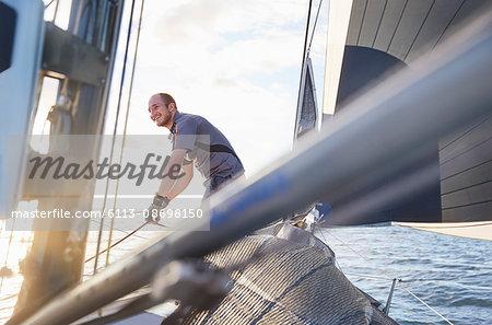 Smiling man sailing holding rigging on sailboat