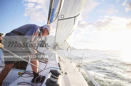 Man sailing pulling rigging on sailboat on sunny ocean
