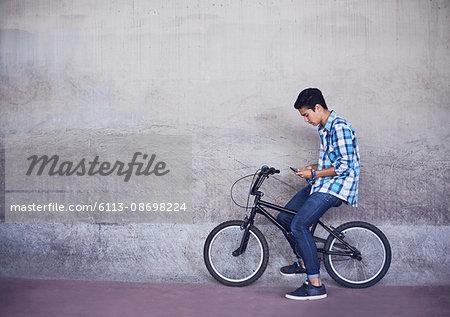 Teenage boy texting on BMX bicycle at wall