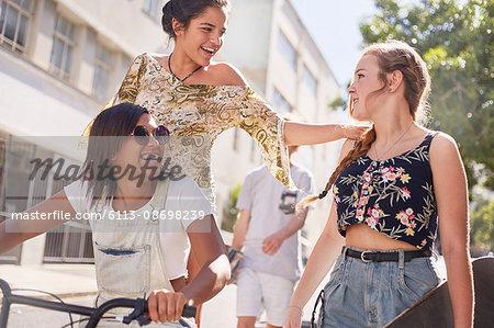 Teenage girls with BMX bicycle and skateboard on sunny urban street