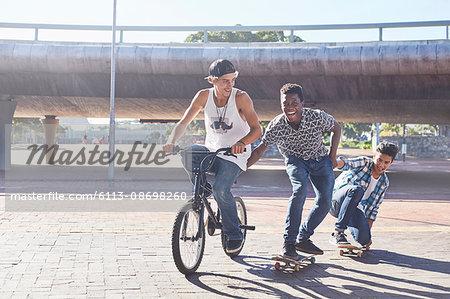 Teenage boys riding BMX bicycle and skateboarding at sunny skate park