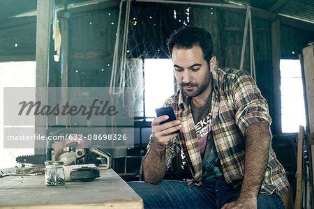 Man browsing internet with smartphone during work break