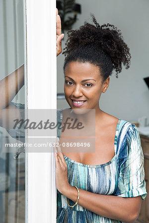 Woman leaning in doorway, smiling, portrait