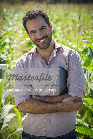 Farmer standing in cornfield