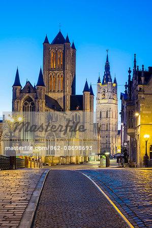 Belgium, Flanders, Ghent (Gent). Sint-Niklaaskerk (Saint Nicholas' Church) and Het Belfort van Gent, 14th century belfry, at night from St. Michael's Bridge.