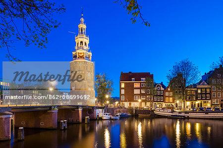 Netherlands, North Holland, Amsterdam. 16th century Montelbaanstoren tower on Oudeschans canal.