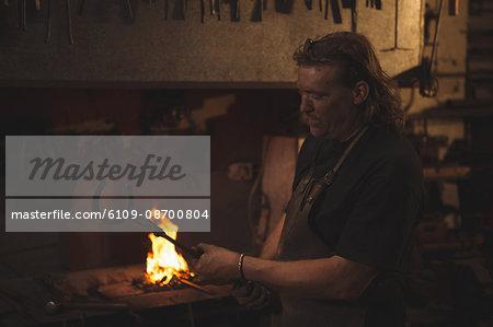 Blacksmith holding metal horseshoe with tongs at work shop