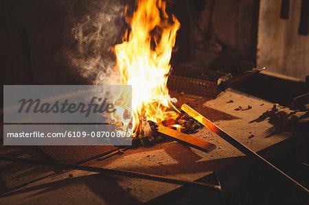 Close-up of blacksmith heats item before forging at work shop