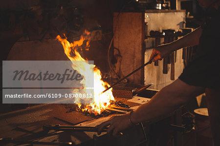 Close-up of blacksmith heating item before forging at work shop