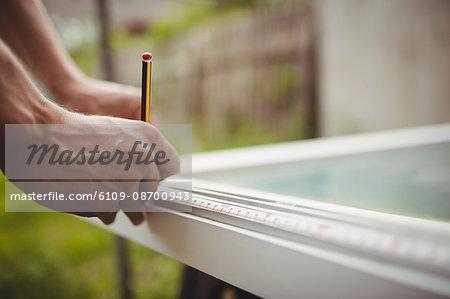 Close-up of carpenter's hands measuring a door frame
