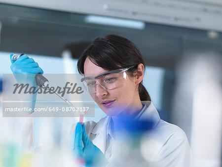 Researcher pipetting DNA sample into eppendorf vial in laboratory