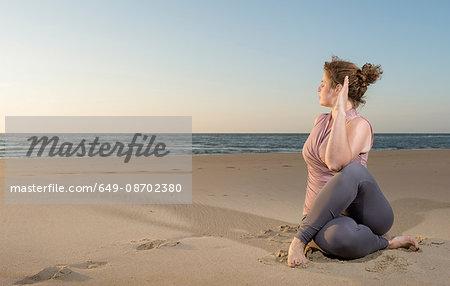 Mature woman practising yoga on a beach at sunset, sitting cross legged