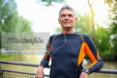 Senior male runner leaning against river footbridge