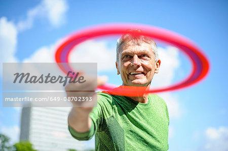 Senior man throwing flying ring against blue sky