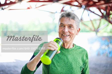 Senior male runner drinking from water bottle under bridge