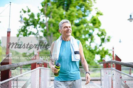 Senior male runner with water bottle crossing  footbridge