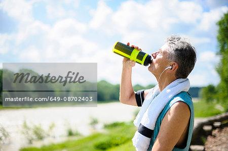 Senior male runner drinking from water bottle by river