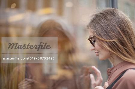 Beautiful woman gazing at shop window, Freiburg, Germany