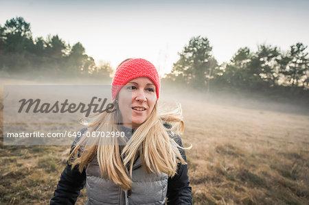 Woman on misty open field, Augsburg, Bavaria, Germany