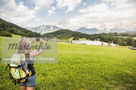Woman taking photograph of Karwendel mountains, Gerold, Bavaria, Germany