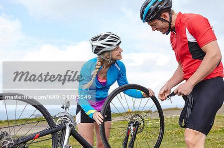 Cyclists fixing wheel on roadside