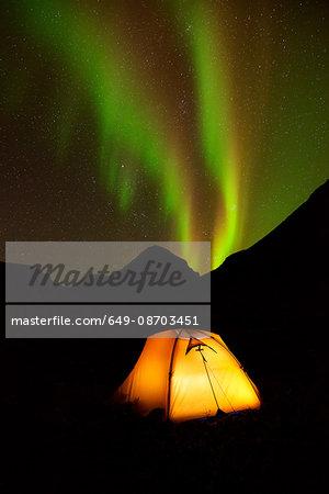 Illuminated tent and Aurora borealis at night, Khibiny mountains, Kola Peninsula, Russia