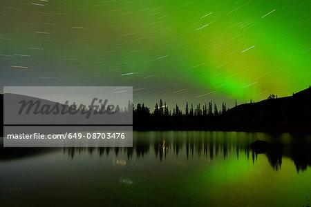 Swirling stars and aurora borealis at Polygonal Lakes at night, Khibiny mountains, Kola Peninsula, Russia