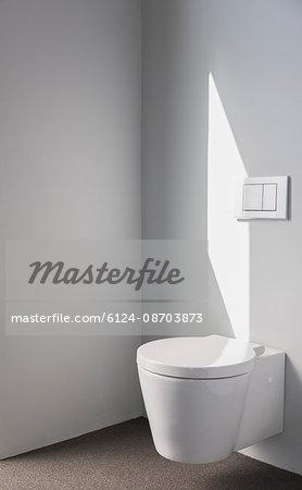 Sunlight on wall above modern toilet in bathroom