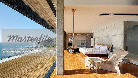 Modern luxury bedroom open to patio with sunny ocean view