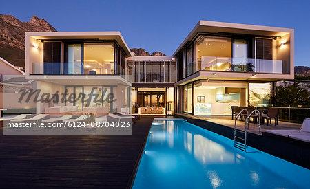 Modern luxury home showcase exterior and swimming pool illuminated at night