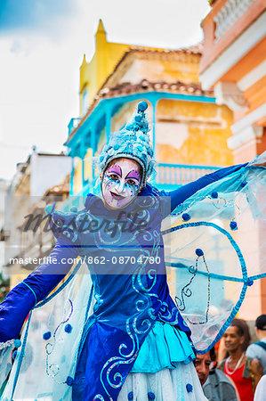 Cuba, Havana, Habana Vieja.  A colourful stilt walker pauses to entertain passers-by in a street in Habana Vieja.