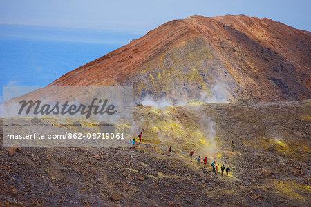 Europe, Italy, Sicily, Aeolian Islands, Vulcano Island,, People walking through fumaroles smoke on Volcano Gran cratere,
