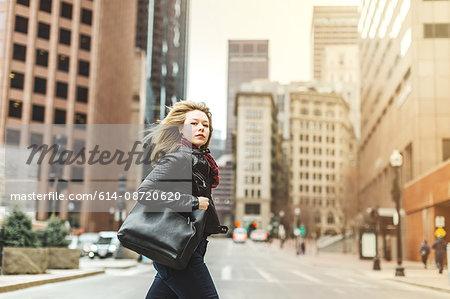 Woman crossing road in urban area, Boston, Massachusetts, USA