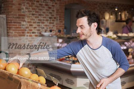 Man shopping reaching for oranges in market