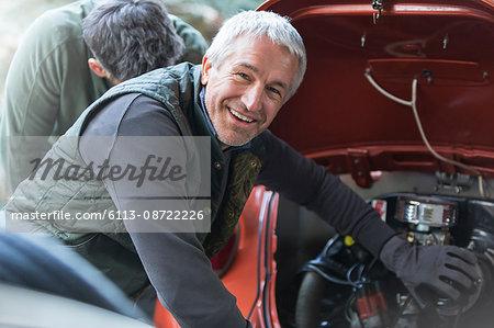 Portrait smiling mechanic fixing engine in auto repair shop