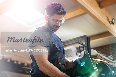 Steel worker using sander in workshop