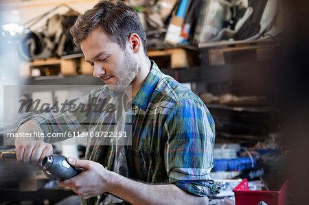 Mechanic fixing car part in auto repair shop