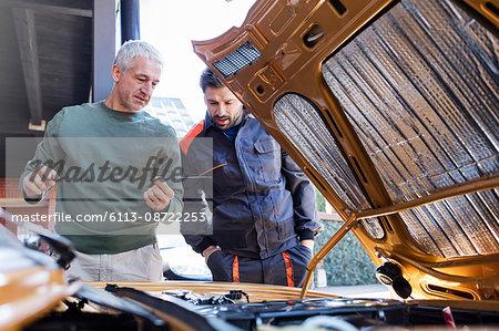 Mechanics checking oil dipstick in auto repair shop
