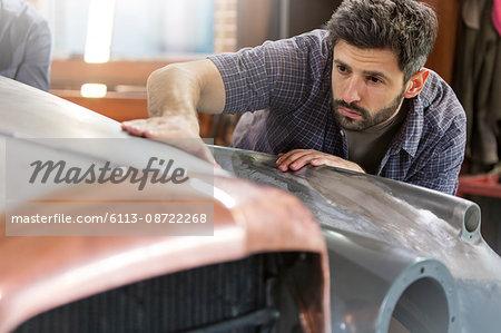 Focused mechanic examining classic car panel in auto repair shop