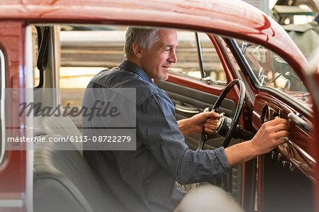 Mechanic inside classic car in auto repair shop