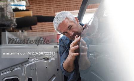 Mechanic examining car panel in auto repair shop