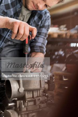 Mechanic fixing car engine at auto repair shop