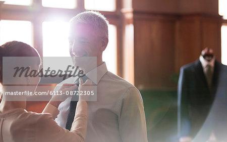 Tailor adjusting tie for businessman in menswear shop