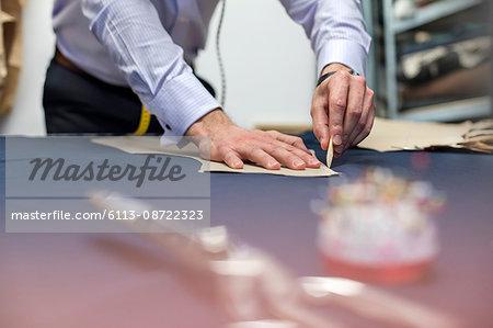 Tailor marking fabric in menswear workshop