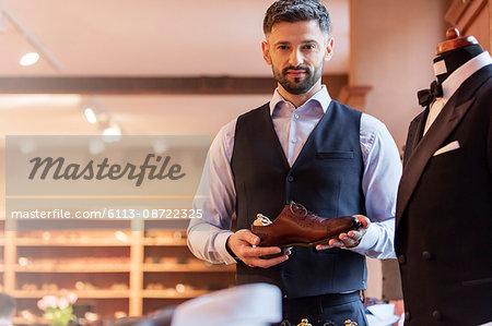 Portrait confident businessman holding dress shoe in menswear shop