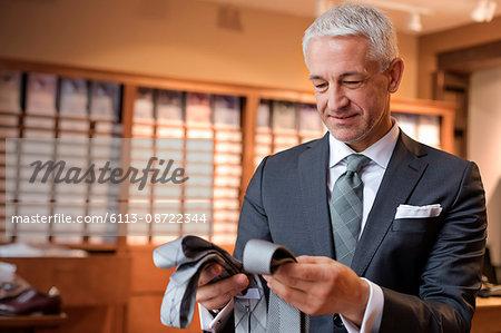 Businessman browsing ties in menswear shop
