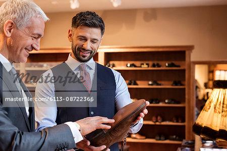 Worker showing dress shoes to businessman in menswear shop