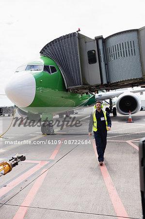 Airport ground crew walking on runway at airport terminal
