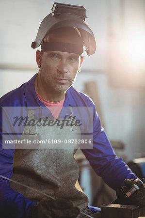 Male welder holding welding torch in workshop